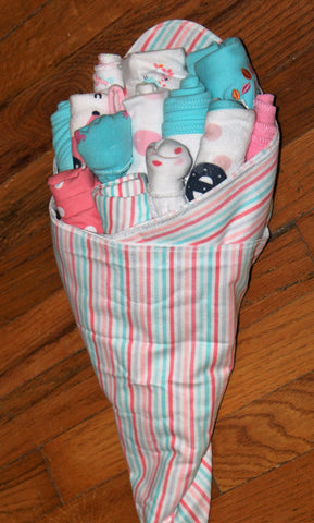A wrapped bouquet of baby items consisting of onesies, bibs, socks, blankets, and burp cloths for a baby girl