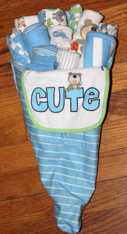 A wrapped bouquet of baby items consisting of onesies, bibs, socks, blankets, and burp cloths.