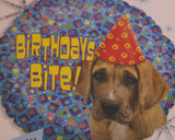 A blue dotted mylar balloon with a sad dog in a birthday hat that says birthdays bite.