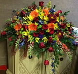 A large arrangement of flowers meant to be on top of a casket during a funeral.