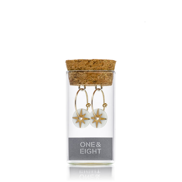 gold star earrings in bottle
