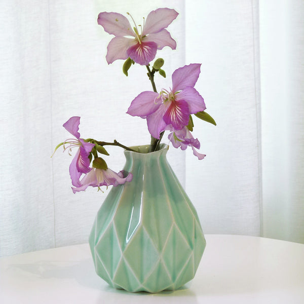 Light green ceramic vase in geometric origami style