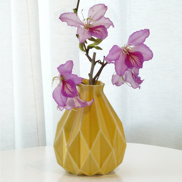Yellow ceramic vase in geometric origami style