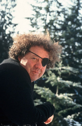 Artist Dale Chihuly in a black shirt surrounded by nature leaning on a railing.