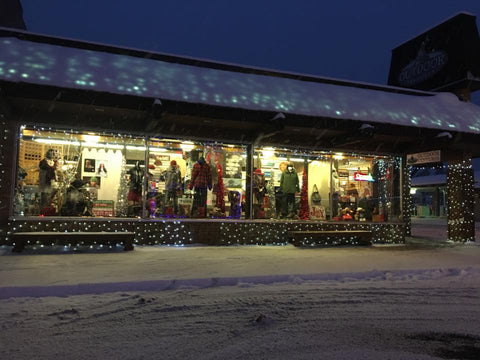Outdoor Ventures - A Lure of Lights snow covered streets store front view