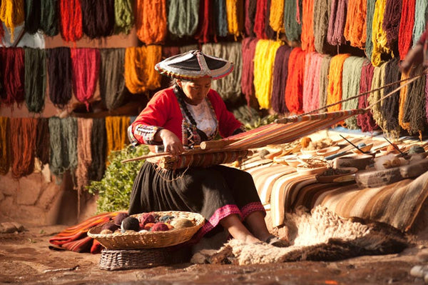 Lady using back strap hand loom to weave a rug. Natural dyed wool in the back.