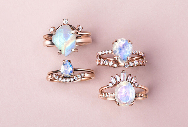 Four Moonstone rings combined with four stackable rings are presented.