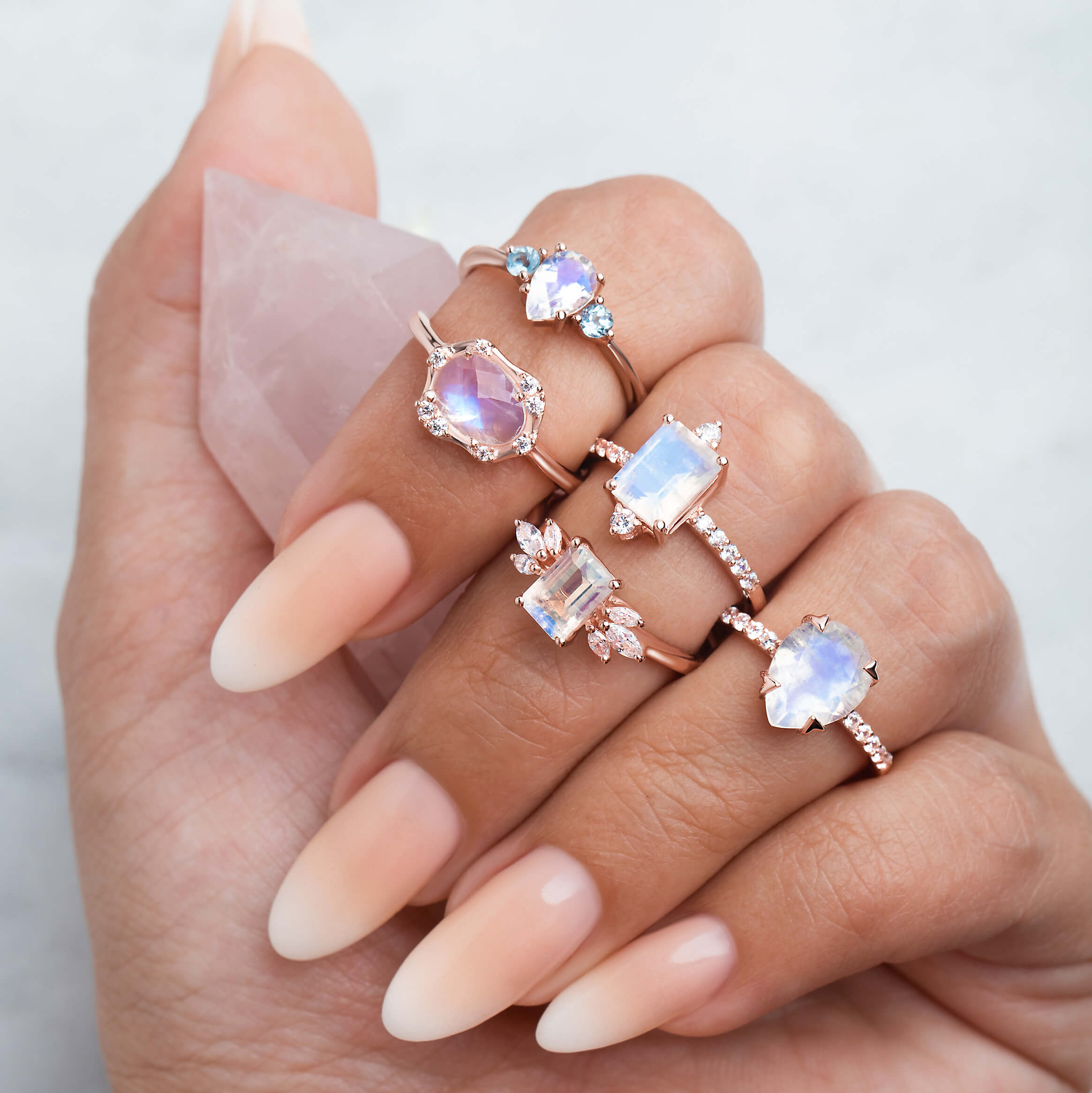 A hand is holding a raw Rose Quartz crystal and is wearing five different gemstone rings.