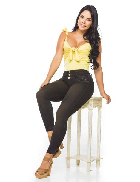 colombian woman sitting down with yellow top and dark wash skinny fit jeans