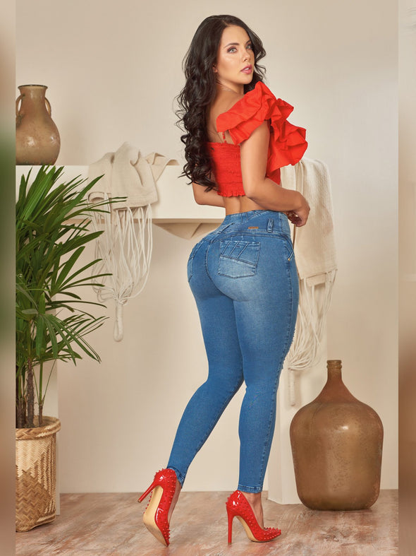back view of colombian model mafe medium wash skinny jeans with red crop top and red high heels
