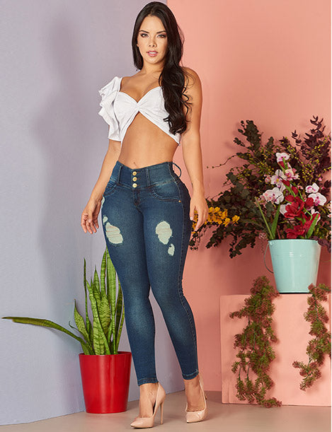 beautiful colombian girl wearing white crop top belly shirt and butt lifting distressed colombian jeans with pair of nude heels