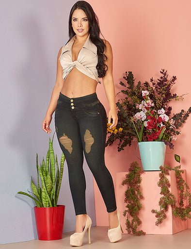latina woman wearing high waist dark wash jeans with distressing, crop top and nude heels