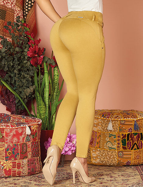 up close view of no pocket yellow mustard color jeans with heels leg up pose