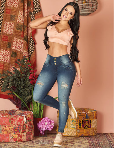 dark hair colombian woman wearing pink crop top and jeans mix with light and dark denim with sneakers
