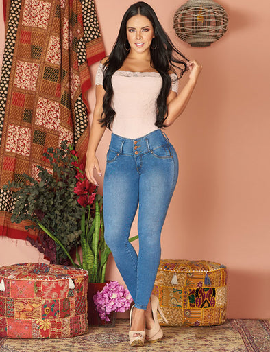 dark hair latina woman touching her hair with blush shirt and high waist colombian blue jeans