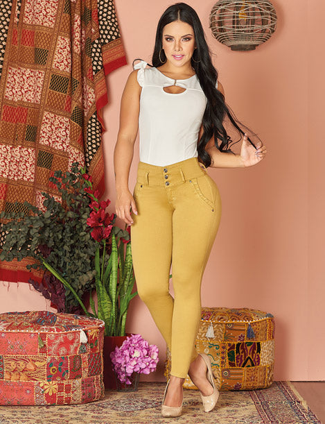 dark hair colombian woman wearing mustard jeans and white key hole top with heels