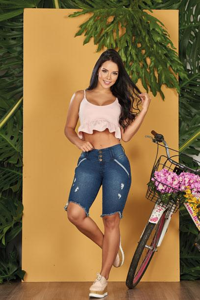 colombian girl with dark hair wearing dark blue butt lift jeans and pink crop top with sneakers bike in background