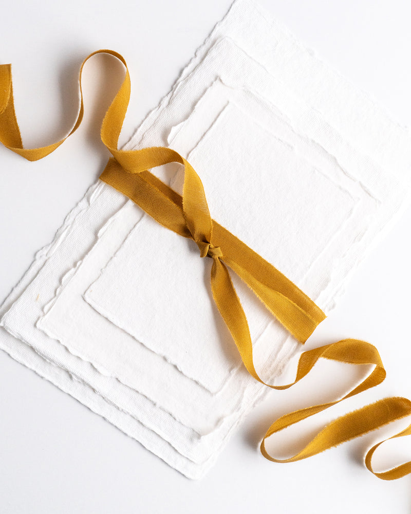 Tono + co Silk Ribbon Trim in Oro. Perfect for stationary styling, boutonnieres, and detail work. Find your inspiration through color and silk. Lovingly hand-dyed in Santa Ana, California and available in 24 signature colors. Check out our website for more styling, flat-lay, and color tips.