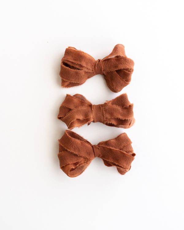 Tono + co Silk Ribbon Trim in Copper. Perfect for stationary styling, boutonnieres, and detail work. Find your inspiration through color and silk. Lovingly hand-dyed in Santa Ana, California and available in 24 signature colors. Check out our website for more styling, flat-lay, and color tips.