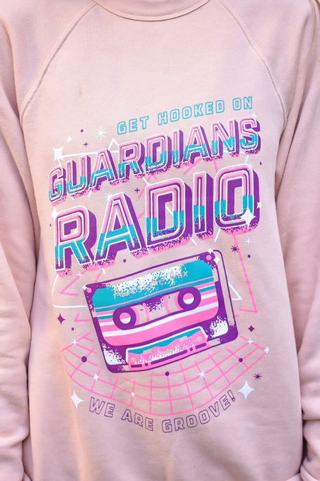Our Guardians Radio design never looked better than in these retro 80s color on this perfect peach colored unisex fleece sweatshirt.