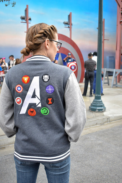 "Donna from Brand By You prepares to get in line for the character meet and greet for Captain America.  She is wearing this two toned fleece letterman jacket that features the classic Avengers character logos surrounding the iconic Avengers ""A"". Captain America is seen in the background at California Adventure."