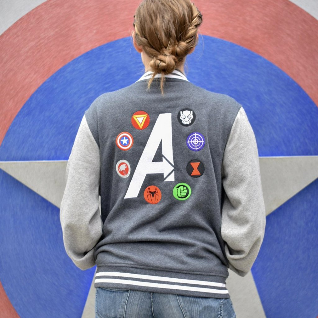 "Brand By You's letterman jacket features the iconic symbols of the classic Avengers crew including Iron Man, Captain America, Thor, Spiderman, Hulk, Black Widow, Hawkeye, and Black Panther. This two toned letterman is fleece and features the design in full embroidery. The front says ""Assemble"" with the A as the iconic Avengers logo. It is a fleece jacket that will keep you warm on colder winter days or cooler park nights."
