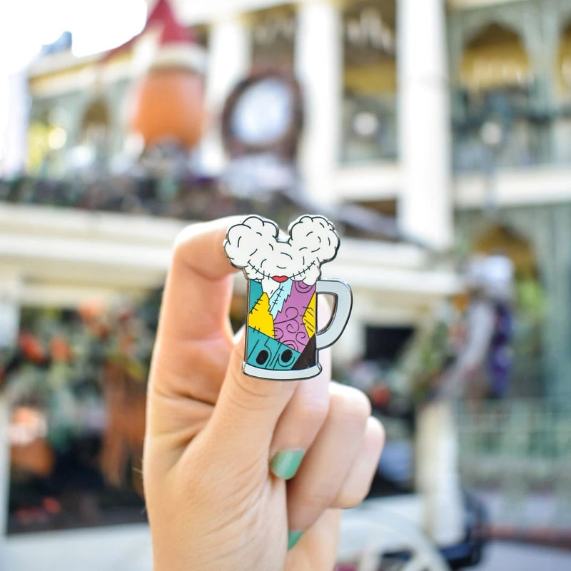 Brand By You's Sally Stitches inspired hard enamel pin has been worked into our classic Mouse Ears and Cold Beers silhouette. This photo was taken in front of the Haunted Mansion Holiday ride at Disneyland. This is the perfect accessory for any pin traders or fans of Nightmare Before Christmas.