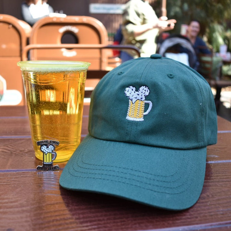 Here is a montage picture of Brand By You's Mouse Ears and Cold Beers dad hat in forest green next to an ice cold beer and one of our matching pins. This picture is to show the realistic size of the pin to the hat, as well as make you thirst for a good beer around the parks!