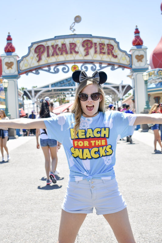 Posing in front of the sign for Pixar Pier! Our Reach for the Snacks sublimated tee is lightweight and super comfortable so you can spend all day in the park in without feeling weighed down.