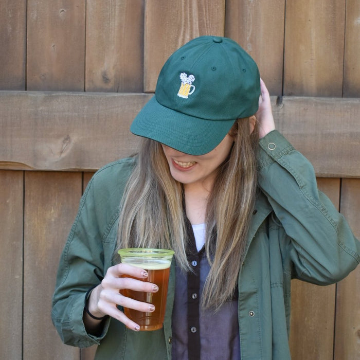 Here is a look at what our Mouse Ears and Cold Beers forest green dad hat looks on a female model. With a sizing clasp in the back, it will fit just about any adult head! The color is perfect for dawning a more rustic or wilderness type of outfit theme which would be great for fall around the parks.