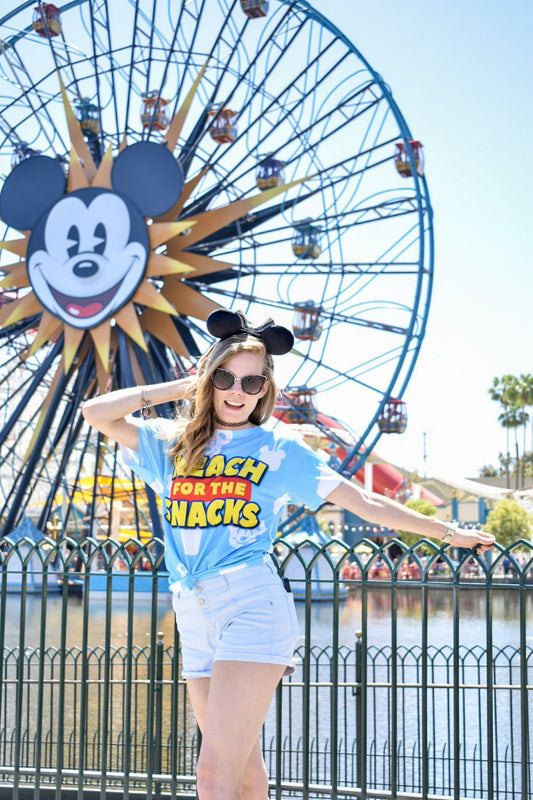 "Posing in front of the Pixar Pal-Around (formerly Mickey's Fun Wheel). It is the perfect background in Pixar Pier for our Toy Story inspired sublimated tee that features a play-on of Woody's famous line ""Reach for the Sky!""."