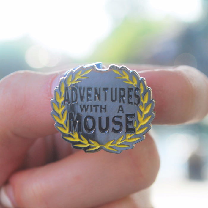 "Silver enamel pin featuring a greek-type plant look around the edges with the words ""Adventures with a Mouse"" being encircled by them. This pin is about 1 inch wide and is perfect to put on your pin lanyard for your next park day full of pin trading."