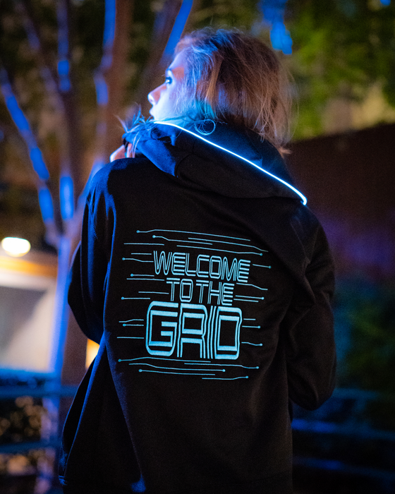 "Light up, glow in the dark zip up hooded jacket features a Tron inspired design. Both the front and the back are embroidered. The front is embroidered with a light disc with grid-like elements stemming out from it. The back features the words ""Welcome to the Grid"" in a Tron font with the same grid-like elements surrounding the words. This picture features the back of the jacket with the ice blue EL/LED piped lining around the hood."