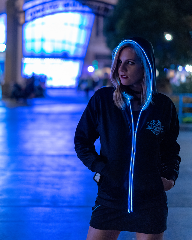 "Light up, glow in the dark zip up hooded jacket features a Tron inspired design. Both the front and the back are embroidered. The front is embroidered with a light disc with grid-like elements stemming out from it. The back features the words ""Welcome to the Grid"" in a Tron font with the same grid-like elements surrounding the words. This picture features a full body shot of the jacket with the ice blue EL/LED piped lining next to the zipper and around the rim of the hood."
