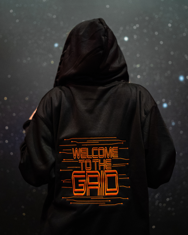 "Light up, glow in the dark zip up hooded jacket features a Tron inspired design. Both the front and the back are embroidered. The front is embroidered with a light disc with grid-like elements stemming out from it. The back features the words ""Welcome to the Grid"" in a Tron font with the same grid-like elements surrounding the words. This picture features the back of the jacket with the orange EL/LED piped lining next to the zipper and around the hood."