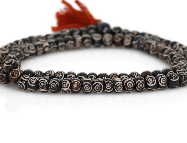 Buddhist Mala Beads with Carved Chakra Symbols Close Up