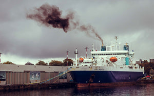 A ship anchored with black smoke coming out its chimney