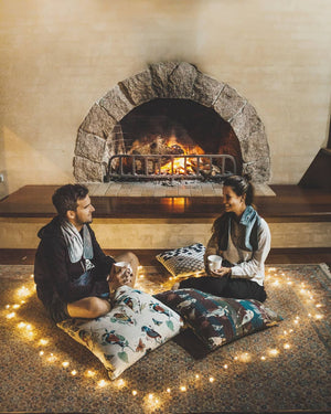 two people sitting by fire with candles shaped as a heart around them
