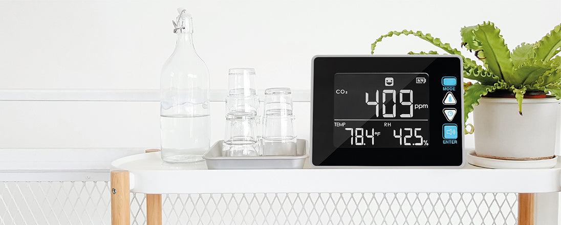 CO2 Meter on a white shelf with green plant aside