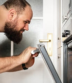 A man is checking an oven