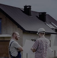 2 people stand in front of a house
