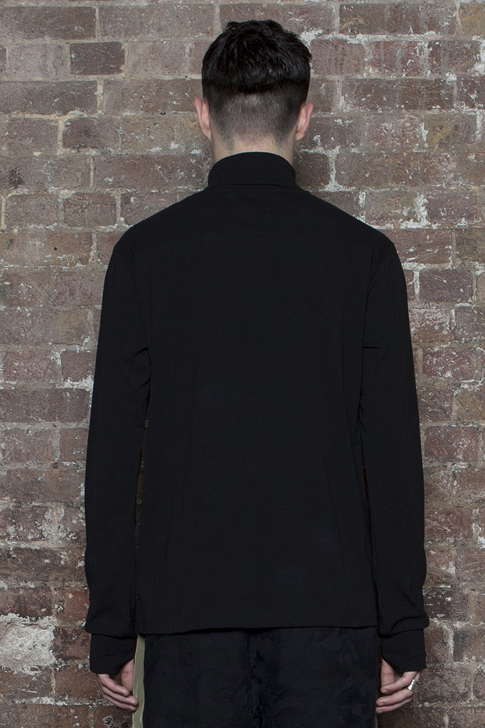 BLACK EYE RAGS - LET IT ROLL IN BLACK, STRETCH CONSTRUCTED ROLL NECK TOP WITH THUMB SLOTS IN THE CUFF.