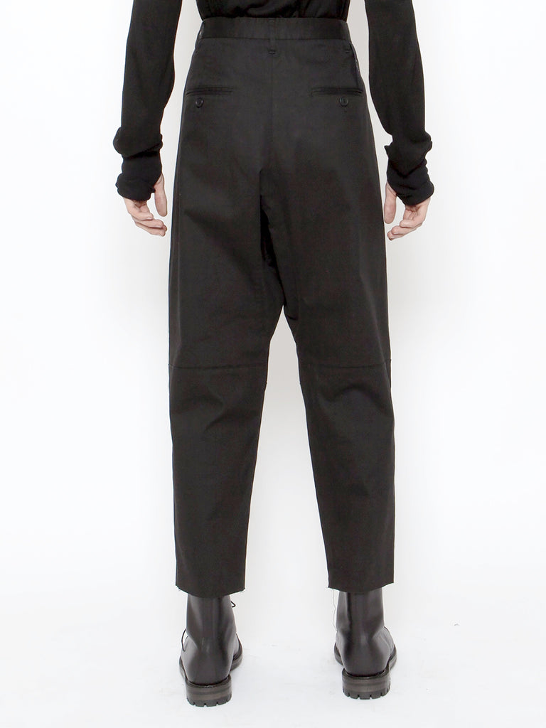 A multi pocket constructed cargo pant. This unique style has been created with a drop crotch, cropped leg loose fit silhouette. The additional front pockets on the front of the thigh and calf feature tonal heavy zips and button fastenings.