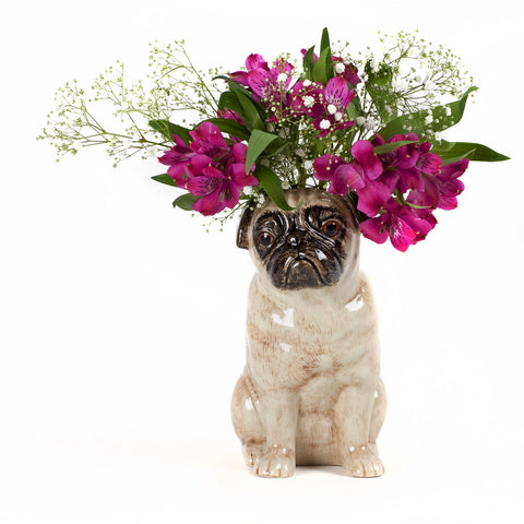 a vase shaped like a pug with pink and white flowers