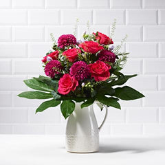 Wide shot of Enchanted in a vase - luxury bouquet of flowers - cerise roses and purple chrysanthemums