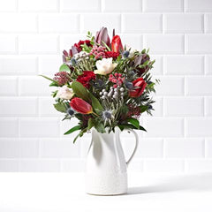 Wide shot of Festive Dream in a vase - luxury Christmas bouquet of flowers - pink roses and red tulips