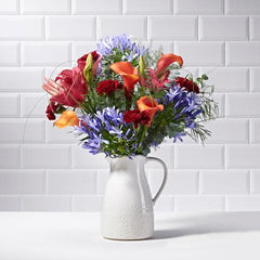 Birds' eye view of Sangria in a vase - luxury bouquet of flowers - red lilies, orange tulips
