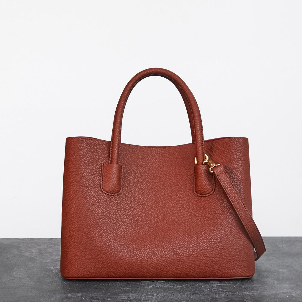 A mid size tote style bag in burnt orange pebbled vegan leather. Shoulder straps and a removable crossbody strap with gold hardware.