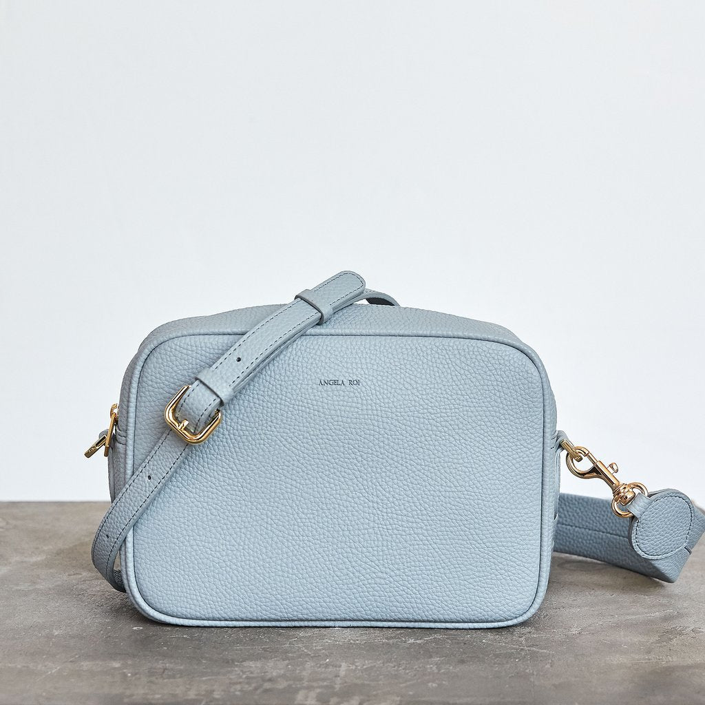 A light powder blue crossbody bag with rounded edges. Gold hardware. Should strap and an adjustable crossbody strap. Gold zipper closure on top.