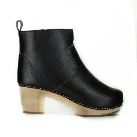 A black vegan leather clog bootie. Ankle height shaft with pull tab in back. Inside zipper closure. Blonde wooden sole. Staples around outsole to connect material to sole.